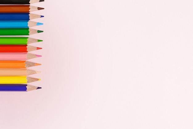 Zurück zu schulkonzept - schulbüroartikel. draufsicht der rosa hintergrundtabelle mit bunten versorgungen und kopienraum. design und kunstkonzept