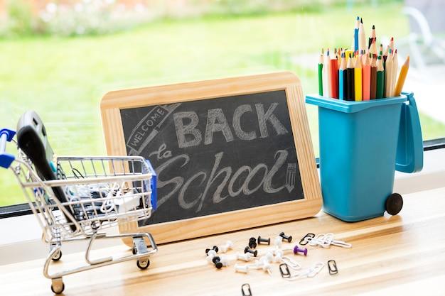 Zurück zum schulhintergrund mit schiefertafel, bleistifte auf mülleimerspielzeug, taschenrechner auf einkaufswagen