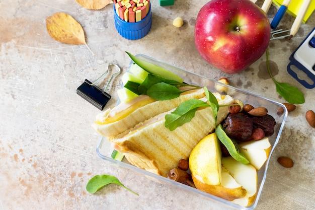 Zurück zum schulhintergrund mit schulbedarf lunchbox und apfel