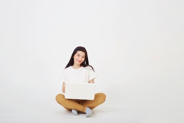 Zurück zum schulkonzept, glückliche junge asiatische frau schönes attraktives sitzen auf dem boden mit gekreuzten beinen und mit laptop