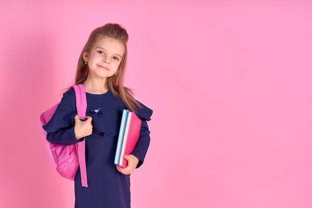 Zurück zum schulkonzept halb gedrehtes fotoporträt des schönen selbstbewussten schönen klugen mädchens mit heftheft, das schuluniformkleid rosa hellen rucksack isoliert trägt