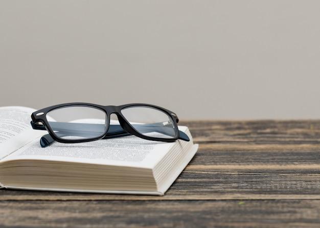 Zurück zum schulkonzept mit brille auf buch auf hölzerner und weißer wandseitenansicht.