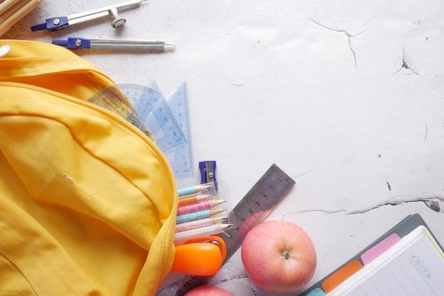 Zurück zum schulkonzept mit gelbem rucksack und schullieferanten auf dem tisch