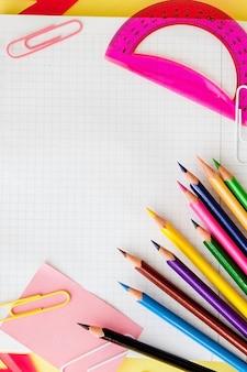Zurück zum schulkonzept mit platz für text. draufsicht. speicherplatz kopieren. schulbürobedarf. kreativer schreibtisch mit buntem briefpapier. farbige büroklammer. schulbedarf auf gelbem hintergrund. büroschreibtisch.