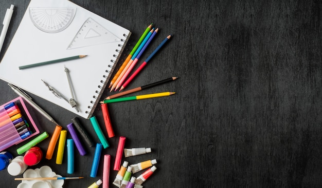 Zurück zum schulkonzept mit zeichenbuch, buntstiften, buntstiften, plakatfarbe, grafiktablett, tastatur, mauscomputer und schulbriefpapier auf schwarzem hölzernem hintergrund mit kopienraum
