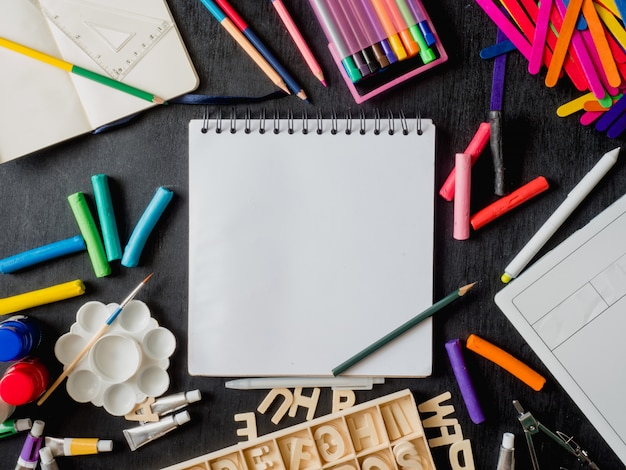 Zurück zum schulkonzept mit zeichenbuch, buntstiften, buntstiften, plakatfarbe, grafiktablett, tastatur, mauscomputer und schulbriefpapier auf schwarzem hölzernem hintergrund