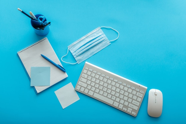Zurück zum schullayoutkonzept. blauer schreibtisch mit kovider medizinischer gesichtsmaske, schreibt notizen, notebook-tastaturmaus am arbeitsplatz. desktop-büroraum-draufsicht. arbeitsplatz bürotisch.