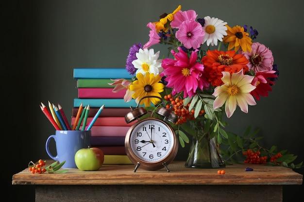 Zurück zur schule. 1. september, wissenstag. der tag des lehrers. stillleben mit herbststrauß und schulmaterial. lehrbücher.