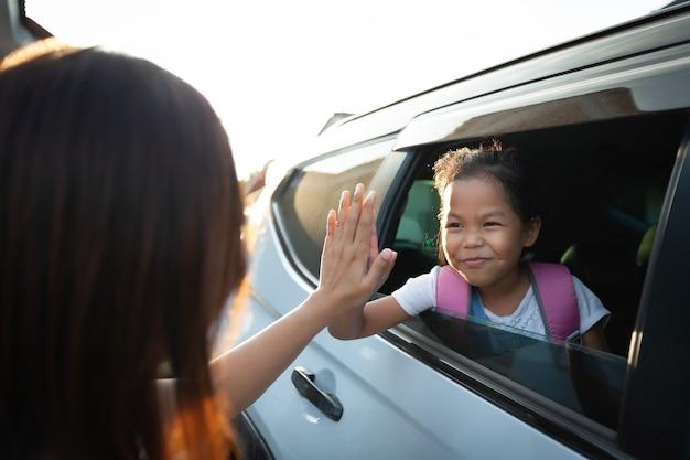 Zurück zur schule. asiatische schülerin mit rucksack, der im auto sitzt und ihrer mutter zum abschied winkt, um sich zur schule fertig zu machen.