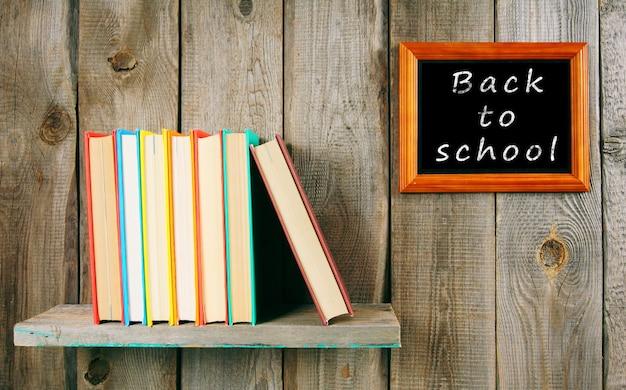 Zurück zur schule. bücher auf einem holzregal und rahmen.