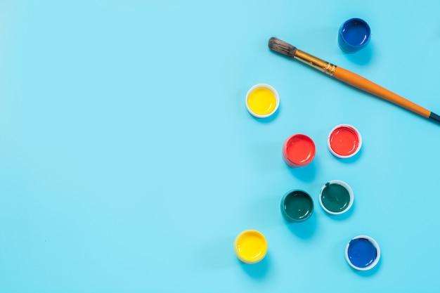 Zurück zur schule. bunte farben und pinsel auf druckvollem blau. kopieren sie platz.