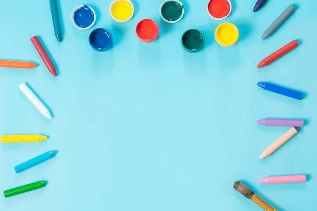 Zurück zur schule. bunter lack und pinsel auf schlagkräftigem blau. kopieren sie platz. ansicht von oben.
