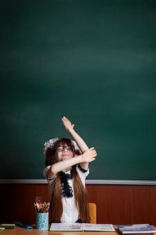 Zurück zur schule. das mädchen am schreibtisch zieht den arm hoch