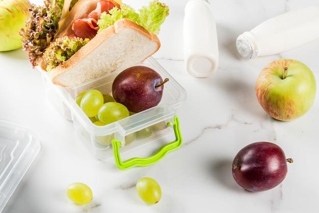 Zurück zur schule. ein gesundes mittagessen in einer schachtel besteht aus frischen äpfeln, pflaumen, trauben, einer flasche joghurt und einem sandwich mit salatblättern, tomaten, käse und fleisch. auf einem weißen marmortisch.