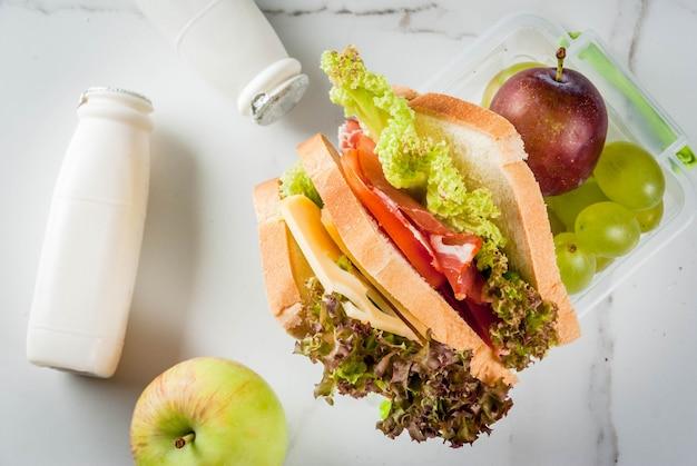 Zurück zur schule. ein gesundes mittagessen in einer schachtel ist frisches obst, pflaumen, trauben, eine flasche joghurt und ein sandwich mit salat, tomaten, käse, fleisch. weißer marmortisch. ansicht von oben