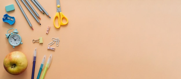 Zurück zur schule. flacher kreativer satz schulbedarf, notizbuch, stifte, laptop, wecker. schulhintergrund im orangefarbenen kopierraum. langes breites banner.