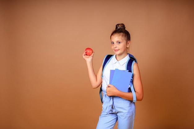 Zurück zur schule. fröhliches glückliches mädchen mit einem blauen rucksack mit apfel