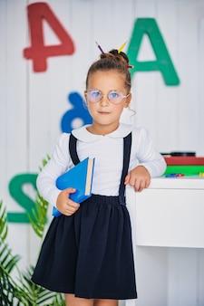 Zurück zur schule. glücklicher lächelnder schüler am schreibtisch. kind im klassenzimmer mit stiften, büchern. kind mädchen von der grundschule. erster tag des herbstes.