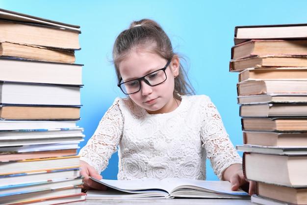 Zurück zur schule. glückliches süßes fleißiges kind sitzt drinnen an einem schreibtisch. kind lernt im unterricht. berge von büchern an den seiten