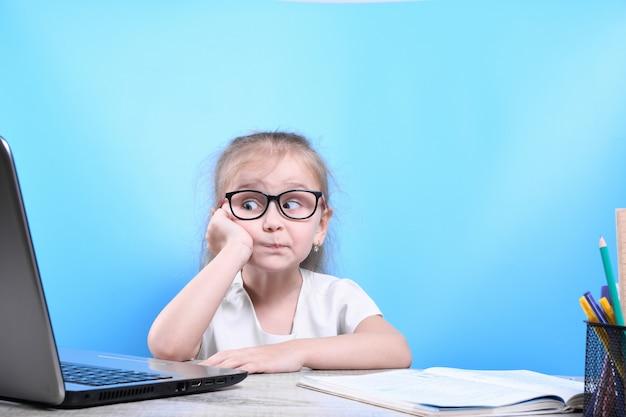 Zurück zur schule. glückliches süßes fleißiges kind sitzt drinnen an einem schreibtisch. kind lernt im unterricht mit laptop, computer