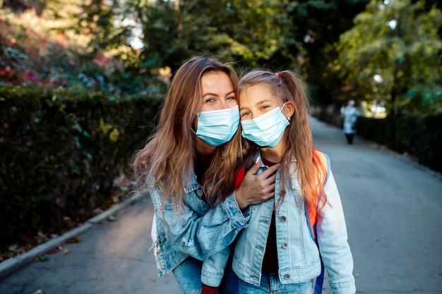 Zurück zur schule. im herbst geht ein 7-jähriges mädchen zusammen mit einer jungen mutter der familie mit gesichtsmasken zur schule.