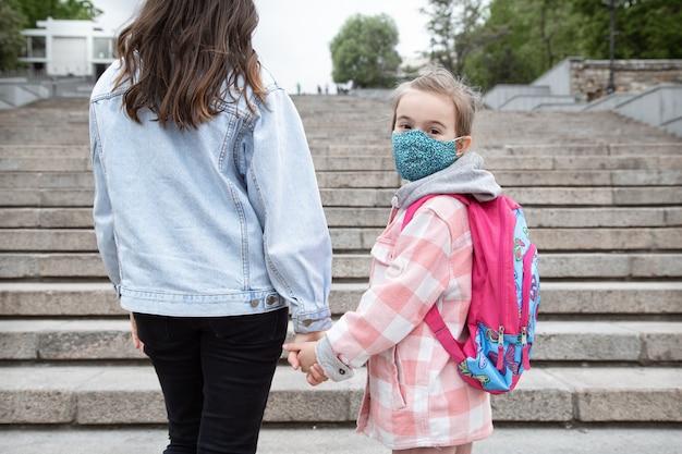 Zurück zur schule. kinder mit coronavirus-pandemie gehen in masken zur schule. freundliche beziehungen zu meiner mutter.