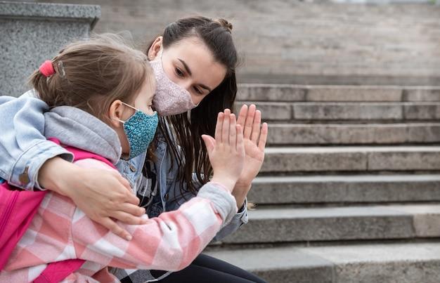 Zurück zur schule. kinder mit coronavirus-pandemie gehen in masken zur schule. freundliche beziehungen zur mutter. kindererziehung.