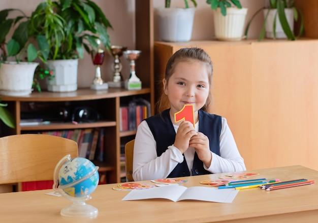 Zurück zur schule. kleines schulmädchen sitzt an ihrem schreibtisch und hält die nummer 1 in ihren händen