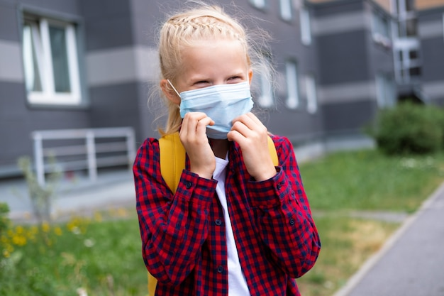 Zurück zur schule. mädchen, das maske und rucksäcke trägt, schützt und sicherheit vor coronavirus. kind, das nach der pandemie zur schule geht.