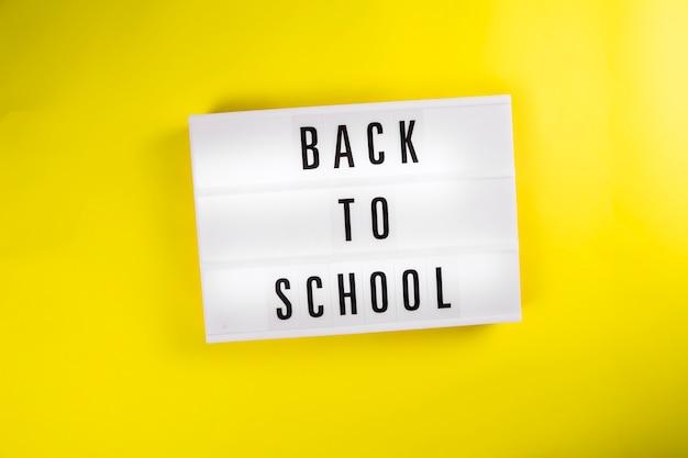 Zurück zur schule nachricht auf leuchtkasten auf gelbem hintergrund isoliert