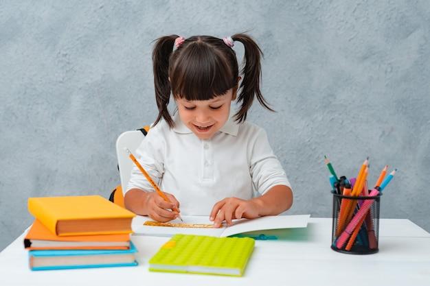 Zurück zur schule. nettes kinderschulmädchen, das an einem schreibtisch in einem raum sitzt.