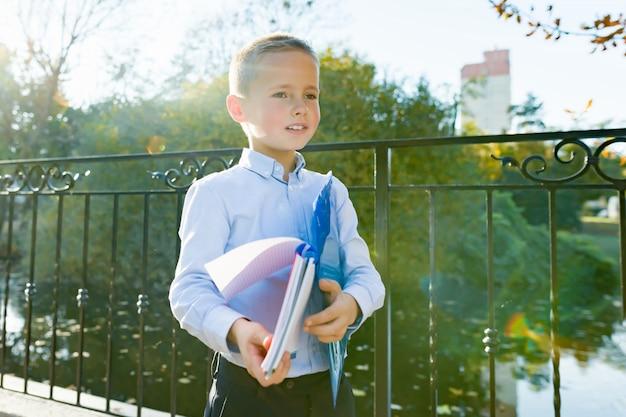 Zurück zur schule, porträt eines jungen mit rucksack, schulmaterial