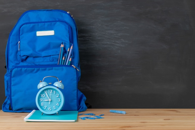 Zurück zur schule. rucksack, wecker und bücher himmelblauer ton auf klassenzimmerschreibtisch mit tafelhintergrund.