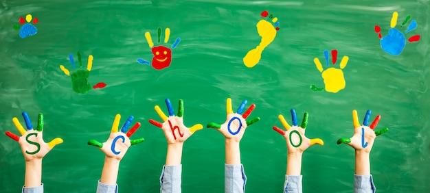 Zurück zur schule schulkinder in klassenhänden gegen grüne tafelbildung und kreativität