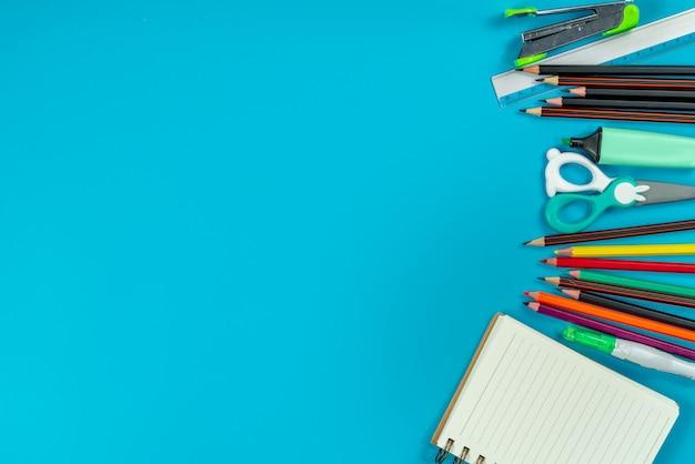 Zurück zur schule . schulmaterial und grüne tafel auf blau
