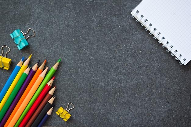 Zurück zur schule. schulmaterial vor dem hintergrund einer dunklen tafel. platz kopieren.