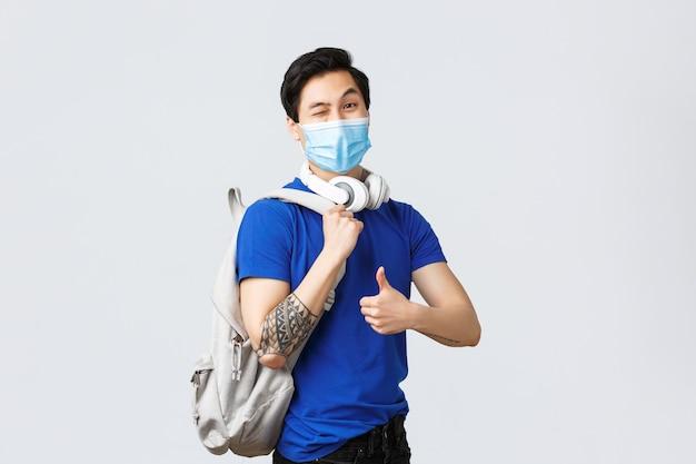 Zurück zur schule, studium des covid-19-, bildungs- und universitätslebenskonzepts. hübscher hipster-typ, asiatischer erstsemester-student in medizinischer maske, daumen nach oben als kopfklassen mit rucksack und kopfhörern zeigen