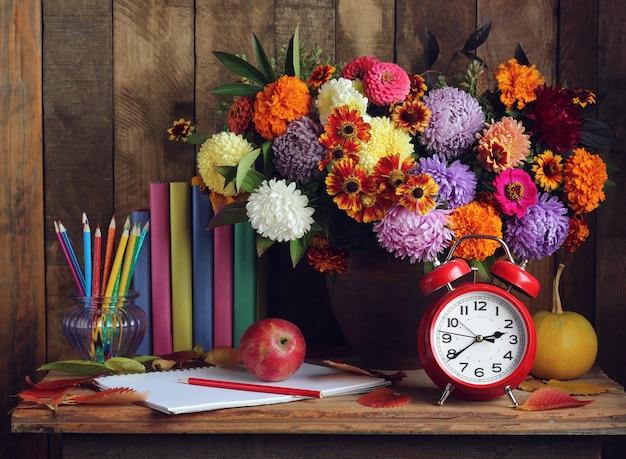 Zurück zur schule. wecker, blumenstrauß, äpfel und bücher auf dem tisch. der tag des lehrers. der tag des wissens