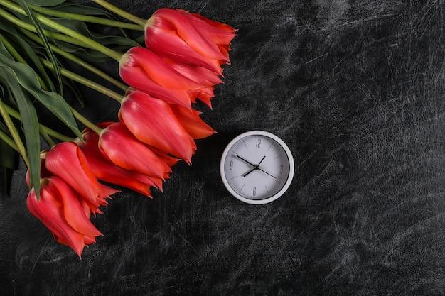 Zurück zur schule. wissen, tag des lehrers. strauß roter tulpen und uhr auf kreidetafel