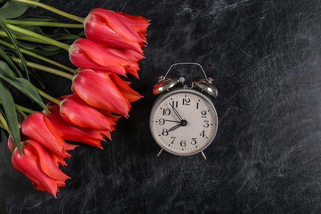Zurück zur schule. wissen, tag des lehrers. strauß roter tulpen und wecker auf kreidetafel. ansicht von oben