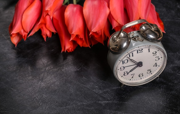 Zurück zur schule. wissen, tag des lehrers. strauß roter tulpen und wecker auf kreidetafel.