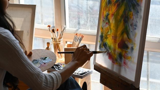 Zurückgeschnittenes bild des jungen schönen künstlers, der einen pinsel hält und auf leinwand malt