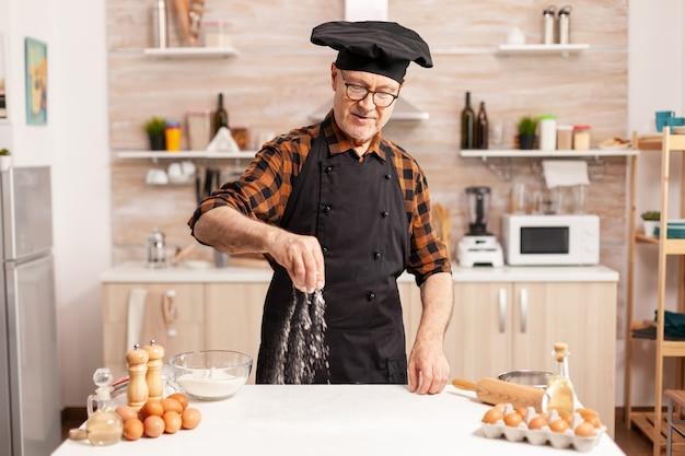 Zurückgezogener bäcker, der schürze trägt und hausgemachte pizza auf dem küchentisch zubereitet. seniorchef im ruhestand mit bone und schürze, in küchenuniform, die zutaten von hand durchsiebt.