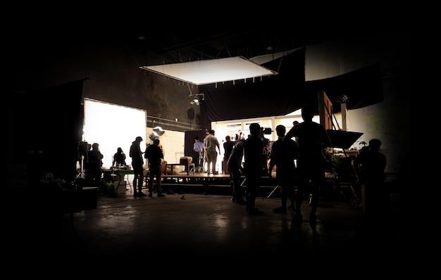 Zurückhaltende silhouettenbeleuchtung der vdo-produktion hinter den kulissen, die das filmteam aufbaut