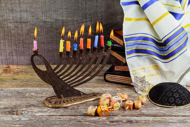 Zurückhaltendes bild jüdischen feiertags chanukka-hintergrundes mit menorah traditionellen kandelabern und brennenden kerzen