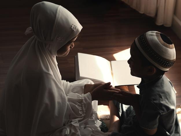Zurückhaltendes bild von religiösen asiatischen muslimischen kindern, die zuschlagen oder grüßen, den koran lernen und den islam studieren, nachdem sie zu hause zu gott gebetet haben. sonnenuntergangslicht scheint durch das fenster. friedliches und wunderbar warmes klima.
