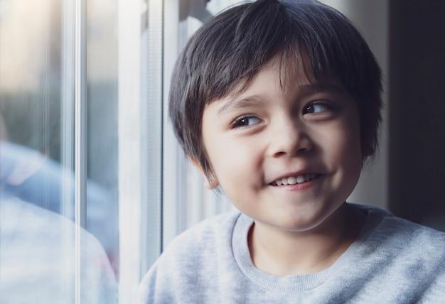 Zurückhaltendes porträt des glücklichen kindes schauend durch fenster mit lächelndem gesicht, netter junge, der lustiges gesicht macht, kind, das sich zu hause während des kühlen wetters draußen im herbst oder im winter entspannt.