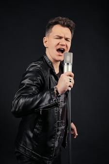 Zurückhaltendes porträt des mannes mikrofon singend und halten