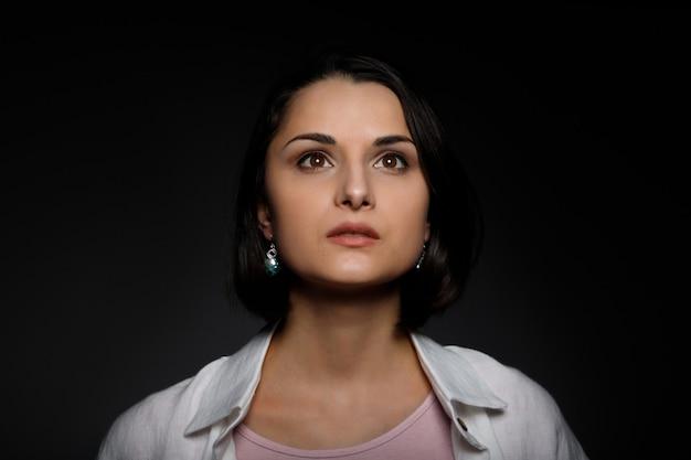 Zurückhaltendes porträt einer ernsten jungen brünetten multiethnischen frau in rosafarbenem panzer und einem weißen hemd, das nach oben schaut