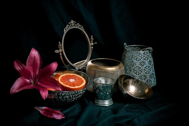 Zurückhaltendes stillleben im kunststil mit antiken dekorationsgegenständen auf dunklem hintergrund. zusammensetzung von vasen, blumen, spiegel, orange mit raum für design. bild für dekorativen laden